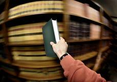 Livro da terra arrendada da mão na biblioteca Foto de Stock Royalty Free