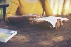 Livro da terra arrendada da mão da mulher a ler imagens de stock