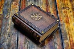 Livro de couro com os símbolos dourados de viquingues fotografia de stock