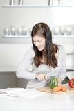 Livro de cozinha da leitura da mulher Imagens de Stock