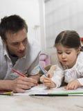 Livro de And Daughter Coloring do pai no assoalho Fotografia de Stock Royalty Free