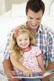 Livro de And Daughter Reading do pai no quarto Foto de Stock Royalty Free