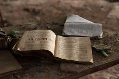 Livro de estudo aberto na tabela de madeira na sala de aula arruinada na escola destruída em Pripyt fotografia de stock