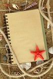 Livro de exercício e estrelas de mar Imagem de Stock
