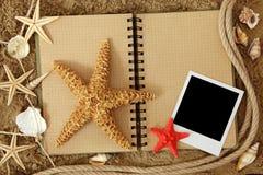 Livro de exercício e estrelas de mar Fotos de Stock