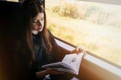 Livro de leitura à moda da menina do moderno na luz da janela no trem Trav foto de stock royalty free