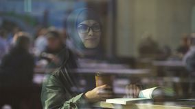 Livro de leitura árabe novo do estudante fêmea no café, preparando-se para o teste, literatura vídeos de arquivo