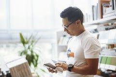 Livro de leitura de óculos novo do homem em livrarias modernas brilhantes foto de stock royalty free