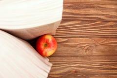 Livro de leitura aberto no fundo de madeira e na maçã vermelha, a vista da parte superior imagens de stock