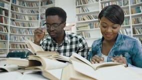 Livro de leitura africano do estudante fêmea quando estudante masculino africano cansado que dorme nos livros, acordando o acima filme