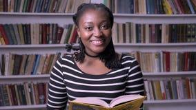 Livro de leitura afro-americano bonito novo da mulher na biblioteca, sorriso, feliz, fundo das estantes video estoque