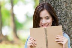 Livro de leitura asiático bonito da mulher no parque Imagens de Stock Royalty Free