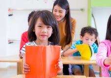 Livro de leitura asiático da criança da menina na sala de aula e quando o professor ensinar fotos de stock royalty free