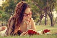 Livro de leitura asiático da menina em parques Fotografia de Stock