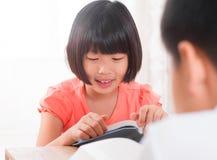 Livro de leitura asiático das crianças em casa imagens de stock