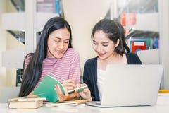 Livro de leitura asiático de duas mulheres na biblioteca imagens de stock royalty free