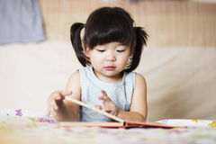 Livro de leitura asiático encantador e bonito da criança foto de stock royalty free