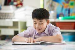 Livro de leitura asiático feliz da criança com cara do sorriso imagem de stock royalty free