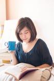 Livro de leitura asiático novo da mulher e café bebendo fotografia de stock royalty free