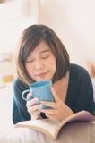 Livro de leitura asiático novo da mulher e café bebendo imagem de stock