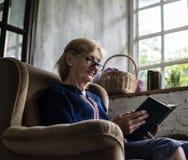 Livro de leitura de assento da mulher caucasiano superior no sofá imagem de stock