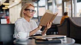 Livro de leitura atrativo da senhora do negócio maduro durante a pausa para o almoço no café vídeos de arquivo