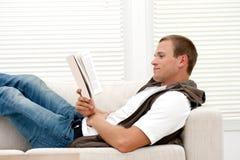 Livro de leitura atrativo de sorriso do homem Fotografia de Stock