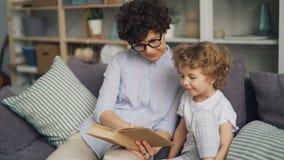 Livro de leitura bonito da criança com sua mãe de amor e sorriso no sofá no plano