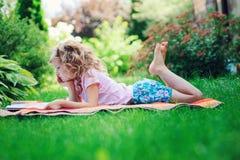 Livro de leitura bonito da menina da criança no jardim do verão exterior Foto de Stock Royalty Free