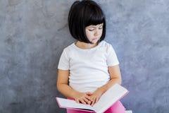 Livro de leitura bonito da menina do cabelo preto pela parede Fotos de Stock Royalty Free
