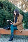 Livro de leitura bonito da menina no parque na mola Imagens de Stock