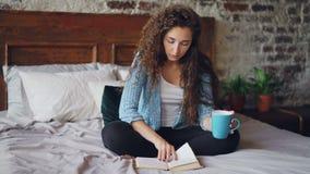 Livro de leitura bonito da menina que senta-se na cama em casa e que guarda o copo com a bebida que aprecia o tempo livre e o des video estoque