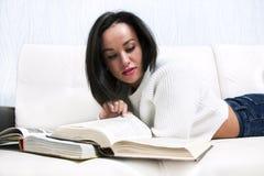 Livro de leitura bonito da moça que encontra-se no sofá fotografia de stock