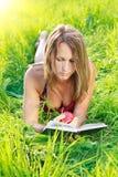 Livro de leitura bonito da mulher com Apple à disposicão Imagens de Stock