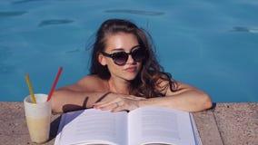 Livro de leitura bonito da mulher na piscina Vista superior vídeos de arquivo