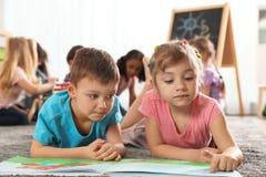 Livro de leitura bonito das crianças no assoalho quando outras crianças que jogam junto fotografia de stock royalty free