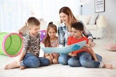 Livro de leitura bonito das crianças pequenas no assoalho foto de stock