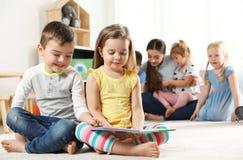 Livro de leitura bonito das crian?as pequenas junto dentro Aprendizagem e jogo foto de stock