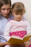 Livro de leitura bonito das irmãs Fotografia de Stock Royalty Free
