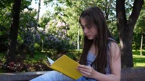Livro de leitura bonito do adolescente que senta-se no banco no parque, estudo exterior Tiro das imagens de vídeo de HD da estáti video estoque
