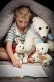 Livro de leitura bonito do rapaz pequeno com seus brinquedos favoritos Imagens de Stock Royalty Free