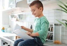 Livro de leitura bonito do rapaz pequeno na cozinha fotografia de stock