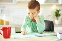 Livro de leitura bonito do rapaz pequeno na tabela foto de stock royalty free