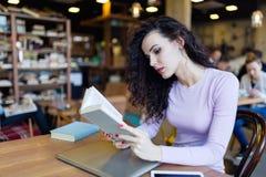 Livro de leitura bonito novo da menina na cafetaria fotos de stock