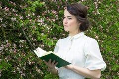 Livro de leitura bonito sonhador da mulher no jardim de florescência da mola Imagem de Stock