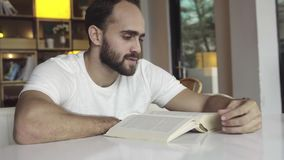 Livro de leitura considerável do homem no café video estoque