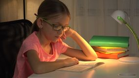 Livro de leitura da criança dos monóculos, menina que estuda na lâmpada de mesa, aprendendo as crianças 4K video estoque