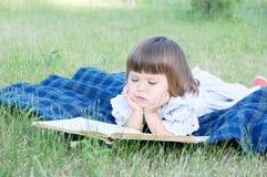 Livro de leitura da criança que encontra-se na menina do estômago, em crianças educação e no desenvolvimento bonitos exteriores,  Fotografia de Stock Royalty Free