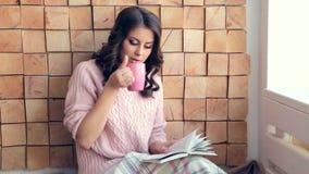 Livro de leitura da jovem mulher em casa e café bebendo video estoque