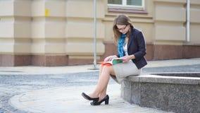 Livro de leitura da jovem mulher em um parque da cidade Moça do estudante que lê um livro vídeos de arquivo